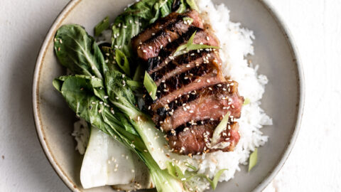 New Zealand beef miso marinated ribeye over white rice with bok choy in bowl