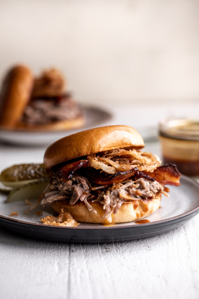 classic pulled pork sandwich made with braised pork bacon, onion rings and cheddar cheese on a brioche bun