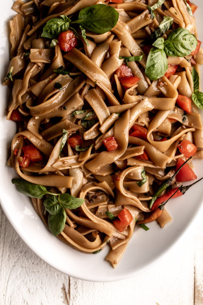 """Drunken noodles or """"Pad Kee Mao"""" - rice noodles are tossed in an easy soy and fish sauce base with garlic, tomatoes and fresh basil leaves."""