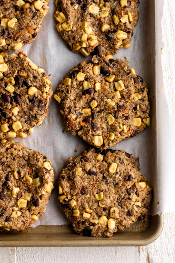 formed spicy black bean and corn veggie burger patties on a baking sheet