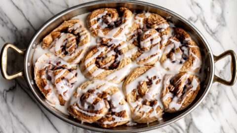apple cinnamon rolls with icing in a oval baking dish