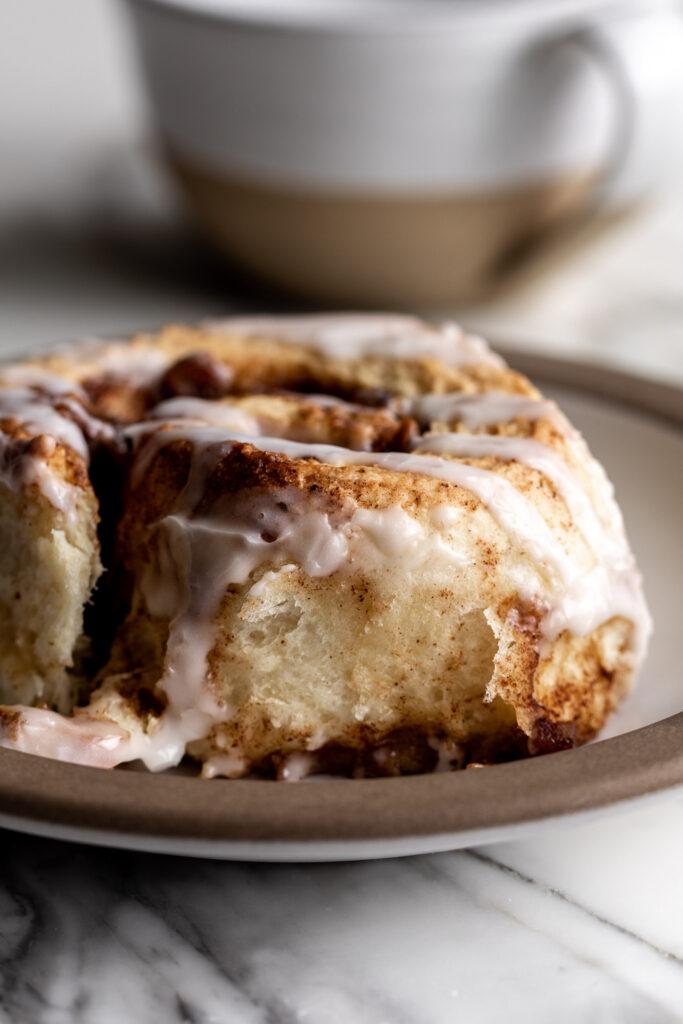 individual apple cinnamon roll on plate with coffee mug